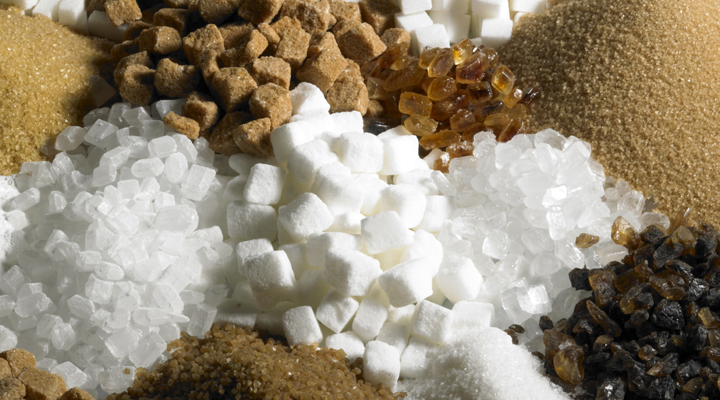 A variety of sugars are shown mixed together including brown sugar, cane sugar, marsh mellows and more.